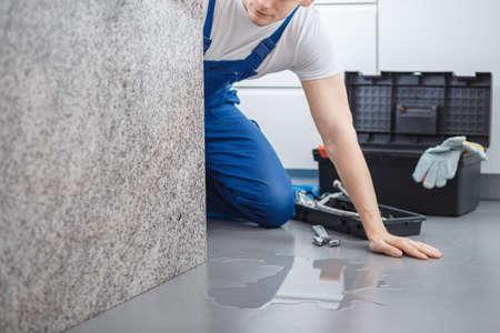 壊れた食器洗い機から床の水を見てツールボックス付き配管工 写真素材