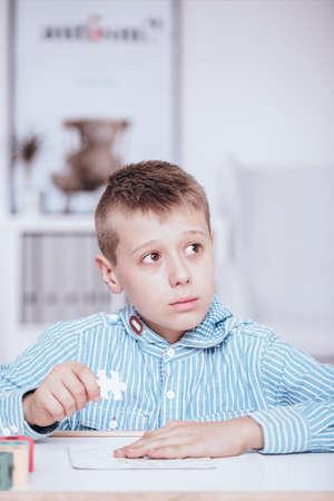 学校でパズルをしているストレスの多い少年のクローズアップ。クラスの概念の間に自閉症の子供 写真素材