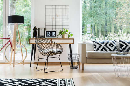 Metal chair at desk with laptop and plant in scandinavian living room with pillows on sofa and bike behind lamp