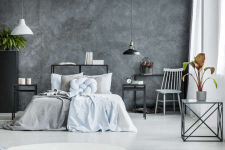 Bright bedsheets on bed between black nightstands in monochromatic bedroom interior with plant on a table