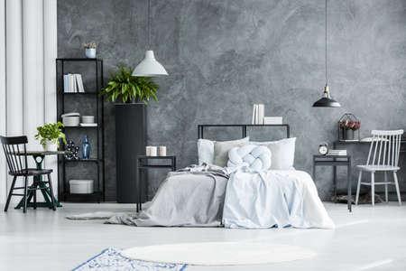 コピースペースを持つコンクリートの壁に対してベッド付きの広々としたベッドルームインテリアの黒と灰色の椅子