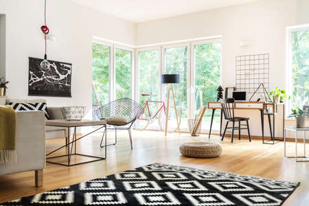 Black and white carpet and pouf in multifunctional living room with workspace, lamps and poster