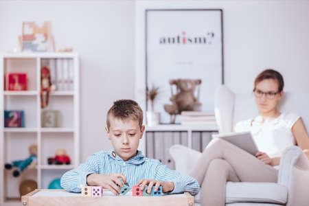 포 그라운드에서 자폐아는 다채로운 큐브로 놀고 카운슬러는 백그라운드에서 행동을 관찰합니다. 스톡 콘텐츠