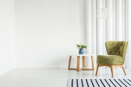 木製のテーブルと空の壁の隣に緑のアームチェアを備えた白いリビングルームのインテリア