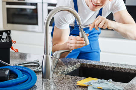Close-up of smiling plumber fixing a faucet with blue pipes on the countertop Stockfoto