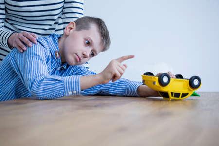 ヘラー症候群の子供は黄色のおもちゃで遊んで、彼の母親は彼を励ます