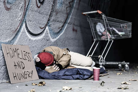 Dirty tramp lying on blanket next to a sign and trolley in the shelter of the city Stock fotó