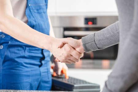 不具合を修復した後、主婦と握手する青いオーバーオールの油圧スペシャリストのクローズアップ