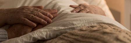 病気の間にお互いを支え合う先輩夫婦の寝具の手のクローズアップ 写真素材
