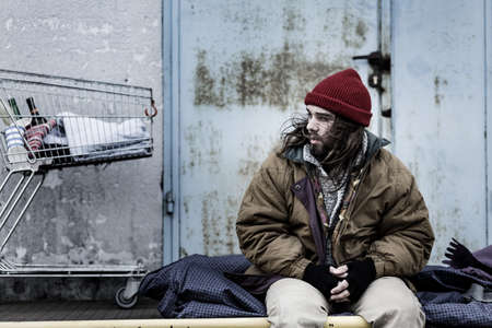 Dirty beggar sitting on a night-bag next to a metal trolley with bottles. Homeless living conditions concept Stock fotó