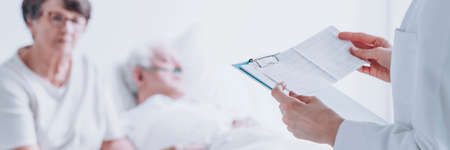 Close-up of doctor holding EKG test results of sick senior patient at the hospital Stock Photo