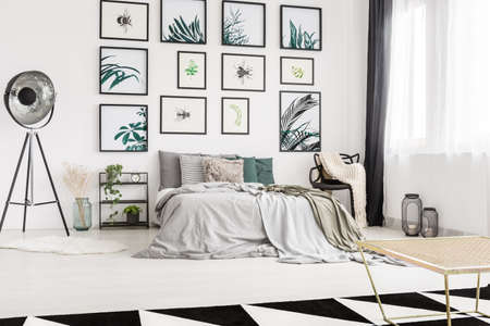 Modern bedroom with nature artwork hanging on a white wall