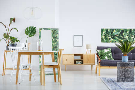 Wooden chairs at table in living room interior with leaves and mockup of poster on white wall above cupboard with lamp