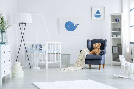 Weiße Krippe, die zwischen einem marineblauen Sessel und einer übergroßen Lampe in einem gemütlichen Kinderzimmer mit nautischem Design steht Standard-Bild