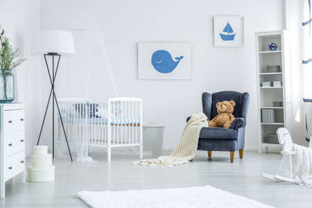 White crib standing between a navy blue armchair and oversized lamp in cozy nursery with nautical design