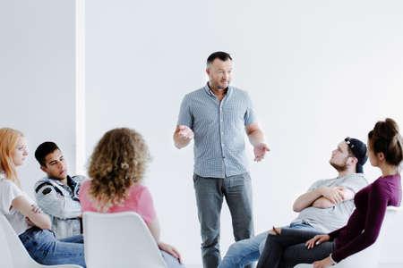 コピースペースのある白いオフィスの円の中に座っている困難なティーンエイジャーに話す心理療法士