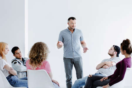 Psychotherapist speaking to difficult teenagers sitting in a circle in a white office with copy space Zdjęcie Seryjne - 93723292