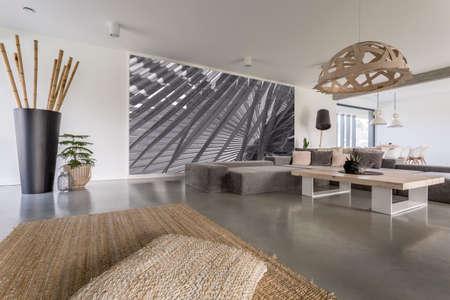 Lampadario decorativo sopra il tavolo progettato in soggiorno con murale grigio sul muro