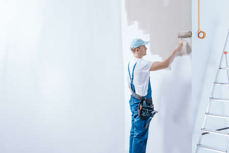 painter in blue overalls painting white wall using roller