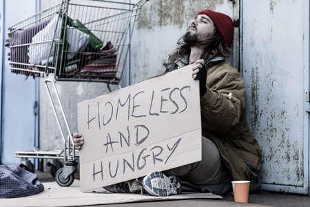 절망적 인 노숙자 및 배고픈 부랑불. 트롤리 옆에 거리에 앉아서 음식과 돈을 구걸하는 표시가 있습니다.