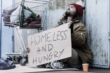 Desperate homeless and hungry tramp with a sign sitting on the street next to a trolley and begging for food and money Banco de Imagens - 93723340