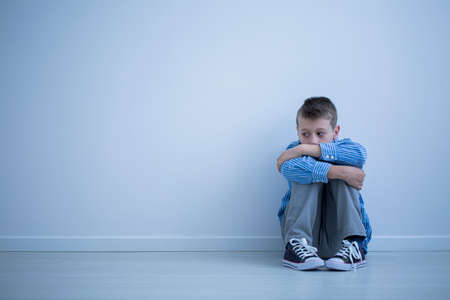 Alienated boy sitting alone on the floor against a wall with copy space. Sad child with autism concept