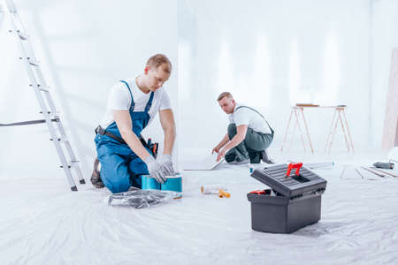 Painter preparing paints and expert arranging tiles on floor. Home renovation crew finishing interior Stock Photo