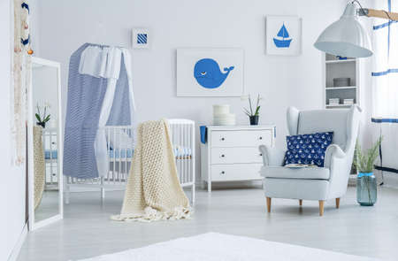 Blue pillow with nautical pattern lying on a white armchair next to wooden crib with beige blanket prepared for a newborn baby