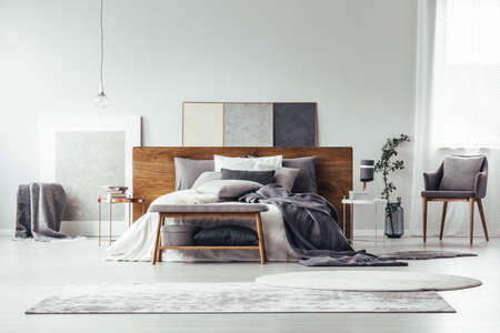 Gray and white rugs in monochromatic bedroom interior with wooden bed, bench and armchair