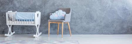 Blauw wolkenhoofdkussen op grijze leunstoel naast witte wieg met blauwe deken tegen concrete muur met exemplaarruimte in de slaapkamerbinnenland van het kind