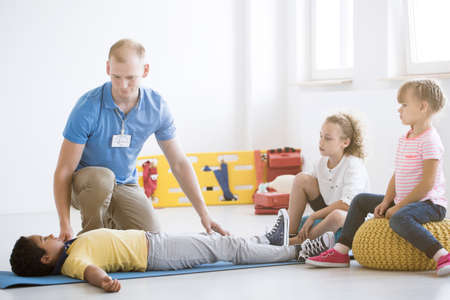 Lifesaver showing safe position to african-american boy during first aid training in the kindergarten Stock Photo