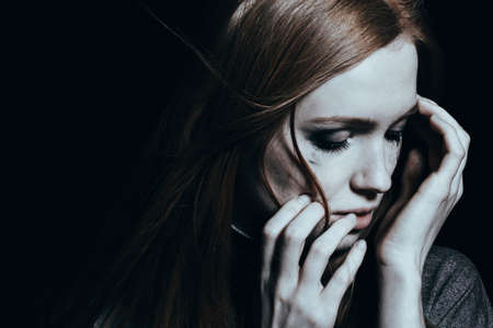 Woman with depression crying against black background with copy space