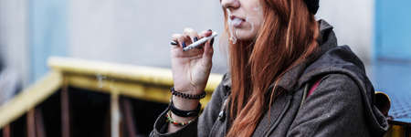 Close-up of red-haired teenager smoking a cigarette. Young girl during maturation period