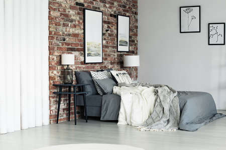 King size grey bed in an apartment with brick wall and pictures
