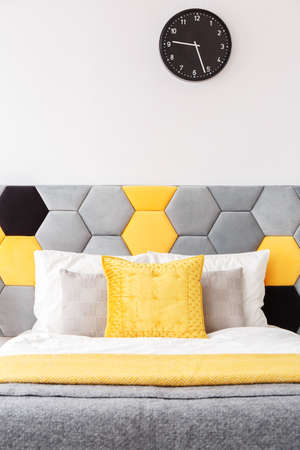 Grey And Yellow Bedsheets On Bed With Bedhead Against White Wall ...
