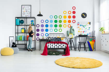 Blonde girl tidying her colorful room with dot stickers on the white wall and round yellow rug