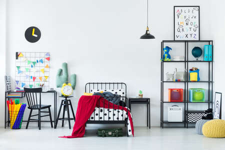 Colorful bedroom for a child with red blanket on metal bed frame and black desk next to a basket with tissue paper Imagens
