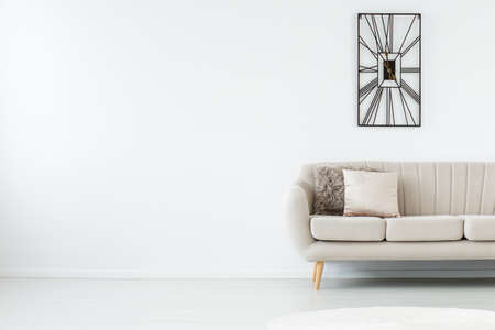 Empty white room with grey sofa and metal black clock on the right