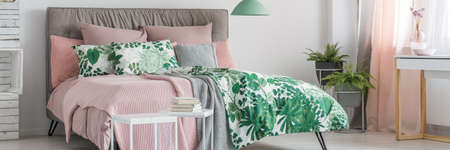 Books on white table in bright bedroom with green lamp above king-size bed with floral bedding