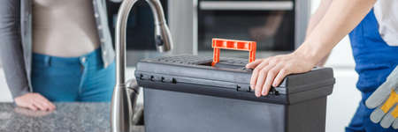 Close-up of plumber's hand on black toolbox next to kitchen's faucet