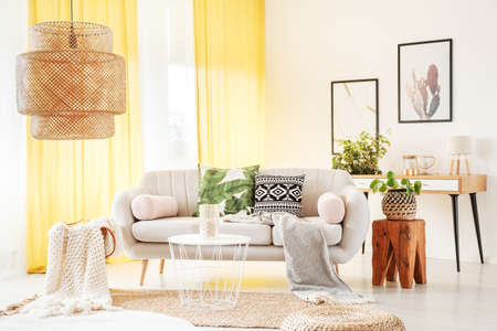 Bright yellow curtains hanging in a stylish boho room interior decorated with rugs, plants and a wooden stool next to a couch
