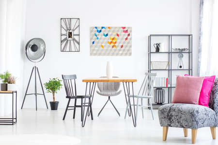 Extra bright white dining room with grey metal furniture and graphic design decoration