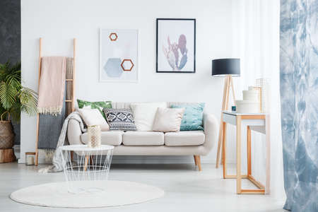Paintings of cactus and hexagons hanging over a cozy sofa with many pillows standing next to a black lamp in living room interior Banque d'images