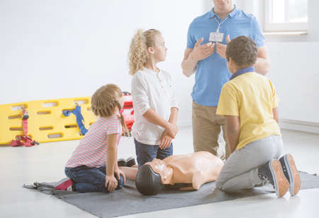 Children listening to a paramedic during first aid training with manikin on grey rug