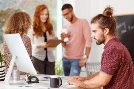 Hombre de negocios enfocado que trabaja en el escritorio con el monitor de la computadora en el espacio abierto de la corporación internacional