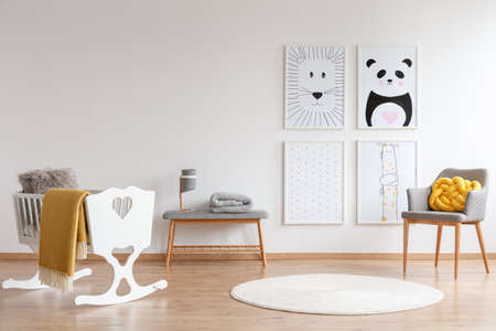 Yellow accents in white and gray bedroom for a baby with round rug and white cradle