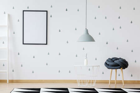 White room with mockup poster and grey raindrops painted on the wall