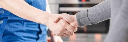 障害を修復した後に握手する専門家とクライアントのクローズアップ
