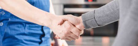 Close-up of expert and client shaking hands after repairing the fault Stockfoto