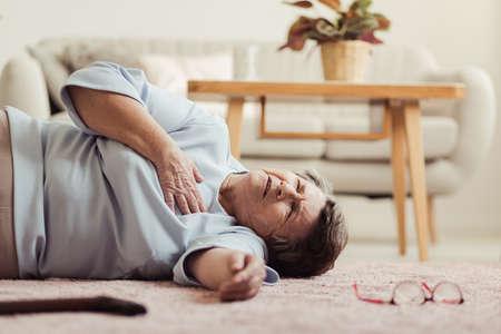 Ältere Frau, die auf dem Boden liegt und einen Herzinfarkt am Erholungsheim hat